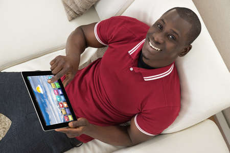 using tablet: Happy Young African Man Sitting On Couch Using Digital Tablet