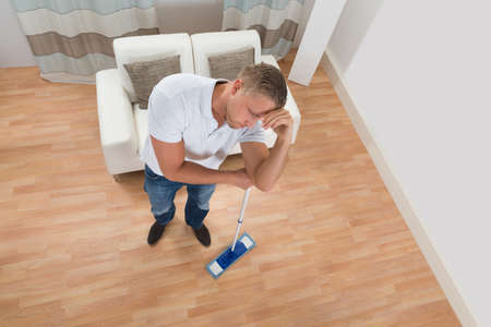 apartment cleaning: Tired Young Man Standing With Mop At Home Stock Photo