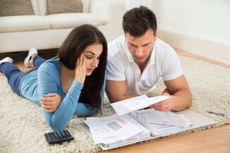 Inquiet jeune couple allongé sur tapis calcul de leurs projets de loi à la maison
