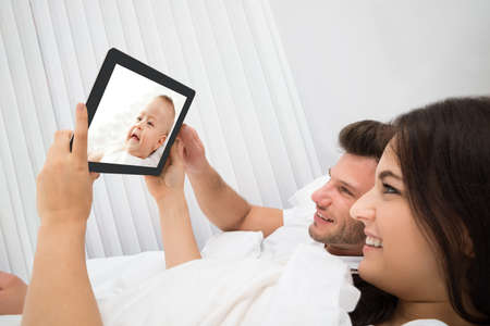 Happy Young Couple On Bed Looking At Baby On Digital Tablet Stock Photo
