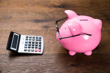 calculadora: Piggybank Con Gafas y calculadora en tabla de madera