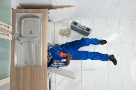 plumber tools: High Angle View Of Handyman Lying On Floor Repair Sink In Kitchen