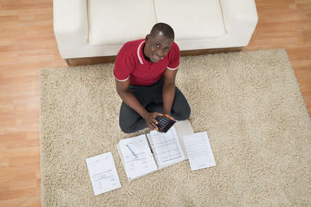 top angle: Portrait Of Young African Man Sitting On Carpet Calculating Invoices Using Calculator Stock Photo