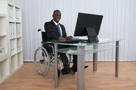 personas sentadas: Retrato de feliz hombre de negocios de África en Oficina sentado en silla de ruedas Foto de archivo