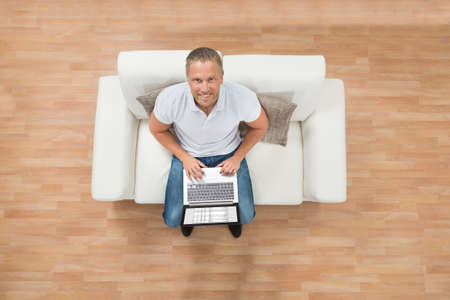 high angle: High Angle View Of Young Happy Man On Sofa Using Laptop Stock Photo
