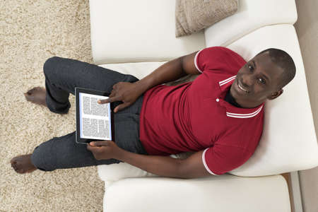 afro man: High Angle View Of Smiling Young African Man Sitting On Couch Holding Digital Tablet