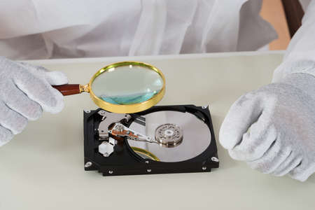 hdd: Close-up Of Person Holding Magnifying Glass Over Harddisk At Desk Stock Photo