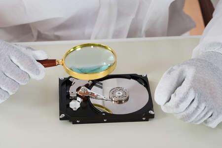 harddisk: Close-up Of Person Holding Magnifying Glass Over Harddisk At Desk Stock Photo