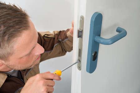 carpintero: Retrato masculino joven carpintero Reparaci�n bloqueo de la puerta Foto de archivo