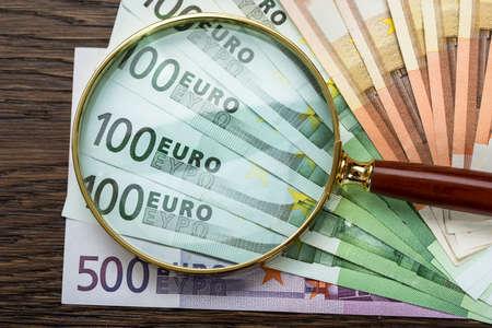 dinero euros: Primer plano de la lupa sobre los billetes en euros Foto de archivo