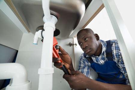 fontanero: Manitas africana joven Reparaci�n Sink Pipe Con herramienta de trabajo
