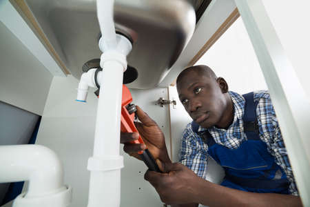 african people: Young African Handyman Repairing Sink Pipe With Worktool