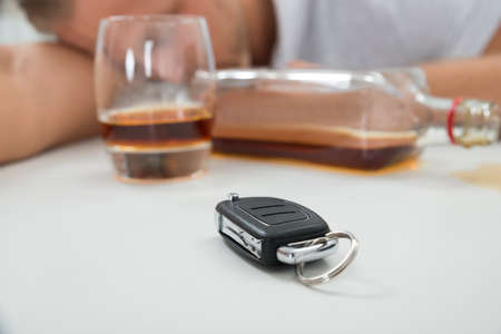 alcohol abuse: Close-up Of Drunk Man With Glass Of Liquor And Car Key
