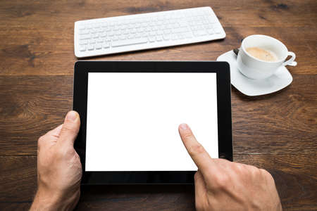 Close-up Of Person Hand Holding Digital Tablet With Keyboard And Tea Cup On Wooden Desk