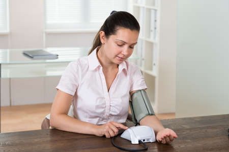 self exam: Young Businesswoman Sitting At Desk Measuring Blood Pressure In Office