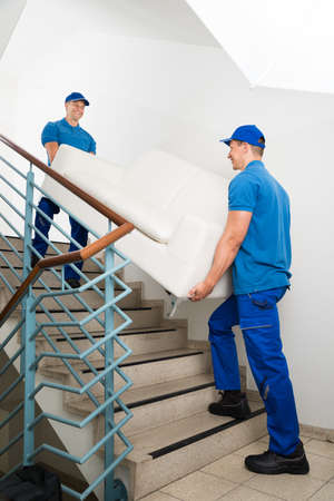 male: Two Happy Male Movers In Uniform Carrying White Sofa On Staircase Stock Photo