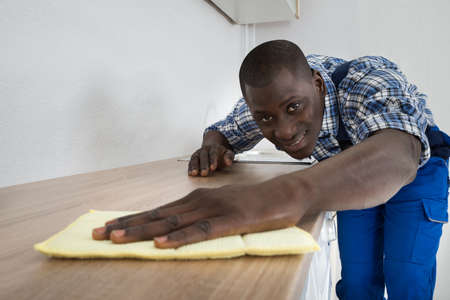 worktop: Young African Man Cleaning Kitchen Worktop Stock Photo