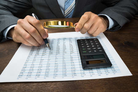 Close-up Of Businessperson Inspecting Financial Data With Magnifying Glass Archivio Fotografico
