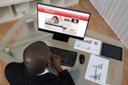 business: Young African Businessman Looking At Business News On Computer In Office