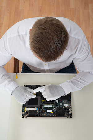 computer devices: High Angle View Of Man Repairing Laptop Motherboard At Desk Stock Photo