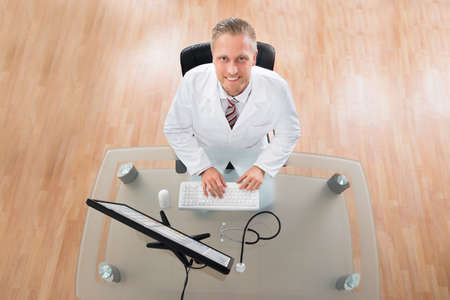 computer desk: Happy Young Doctor Working On Computer At Desk Stock Photo