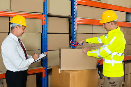 taping: Manager Noting On Clipboard And Worker Taping Box In Warehouse Stock Photo