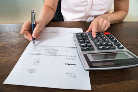 calculating: Close-up Of Female Businesswoman Calculating Tax With Calculator At Desk
