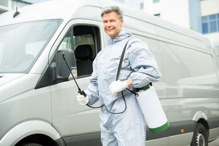 Happy Worker With Pesticide Sprayer Standing In Front Van Zdjęcie Seryjne