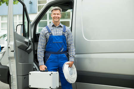 Happy Male Worker With Wire And Toolbox In Front Of Van Stock Photo