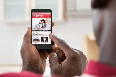 アフリカの若い男は、スマート フォンでニュースを読むのクローズ アップ