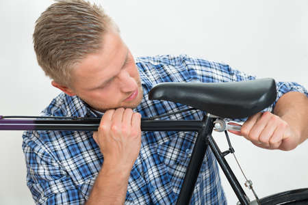 vehicle seat: Portrait Of Young Man Tightening The Bolts Of Bicycle Seat With Spanner