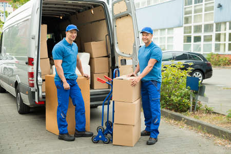 delivery: Two Happy Male Worker In Front Of Truck With Stack Of Cardboard Boxes Stock Photo