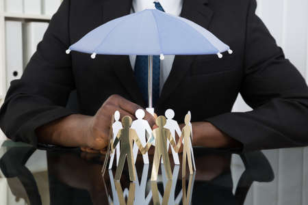 paper cutout: Close-up Of Businessman Hands Holding Small Umbrella Over Paper Cutout People At Desk