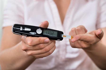 Primer plano de manos de mujer Prueba de alta azúcar en la sangre con glucómetro