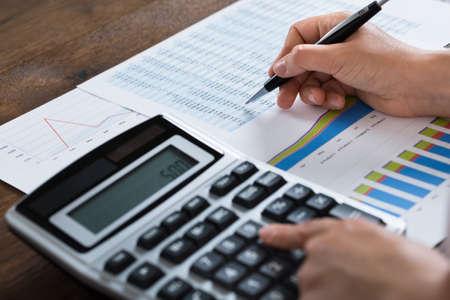 calculadora: Primer De La Empresaria Analizando Informe Financiero Con La Calculadora En El Escritorio de madera
