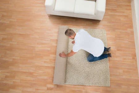 top angle view: Young Man Unrolling Carpet In Living Room