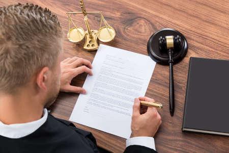 hombre escribiendo: Primer Del Juez escrito en papel en la Sala