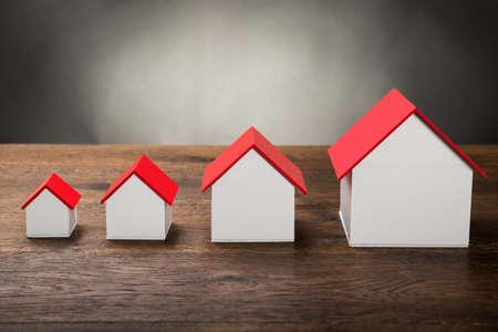 haus: Unterschiedliche Größe Häuser in der Reihe auf Holztisch Lizenzfreie Bilder