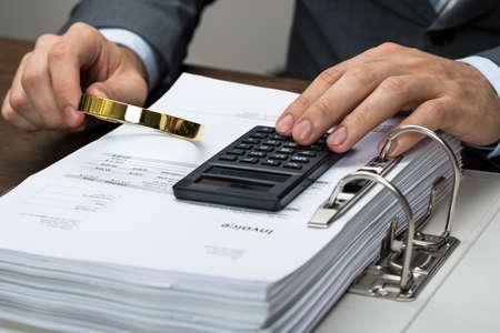 contabilidad financiera cuentas: Primer plano de hombre de negocios Inspección de Recibos Con La Lupa En La Oficina