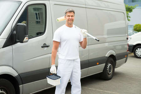 Happy Mature Painter Standing In Front Of Van
