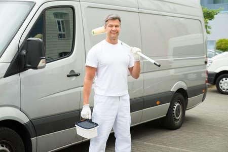 pintor: Feliz maduro pintor se coloca delante de Van Foto de archivo