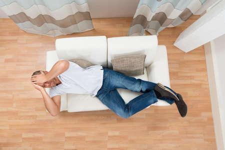 top angle: Young Man Lying On Sofa Having Headache Stock Photo