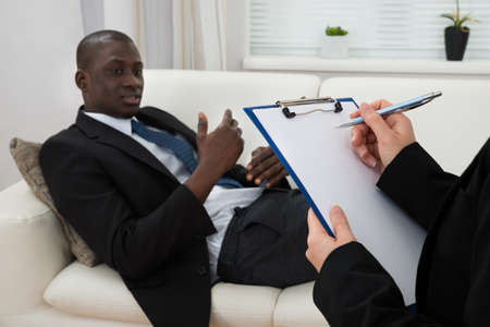 counseling session: African Patient Sitting On Couch And Female Psychiatrist Writing On Clipboard Stock Photo