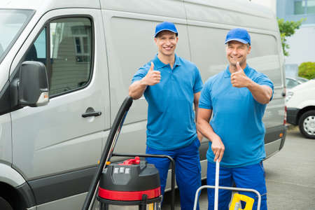 Two Happy Male Cleaners Standing With Cleaning Equipments In Front Van Archivio Fotografico