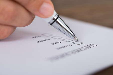 顧客アンケート フォーム上のペンを持つ人の手のクローズ アップ