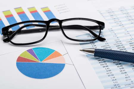 data sheet: Close-up Of A Financial Data Sheet With Eyeglasses And Ballpen