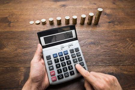 incremento: El hombre de negocios que hace cálculos delante de monedas apiladas