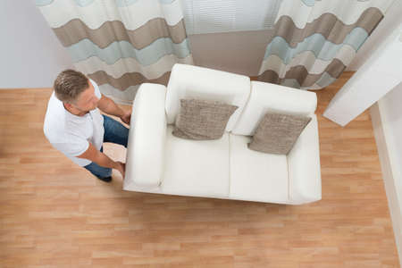furnish: Young Man Lifting Sofa In Living Room Stock Photo