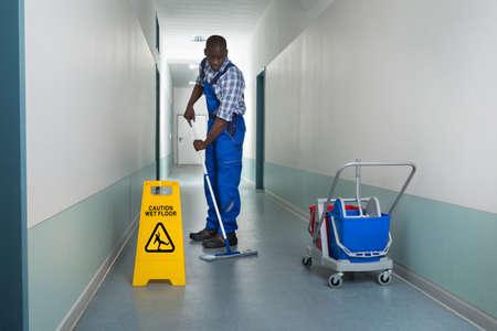 suelos: Joven africano masculino Janitor Planta Limpieza En Corredor