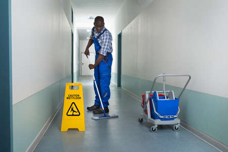 Young African Male Janitor Cleaning Floor In Corridor Imagens